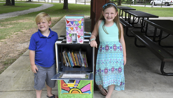 "Lincoln and Grace Bingham stand beside the ""Little Free Library,"" which is now open for business under the pavilion at Richard Wood Park in Thorsby. (Photo by Anthony Richards)"